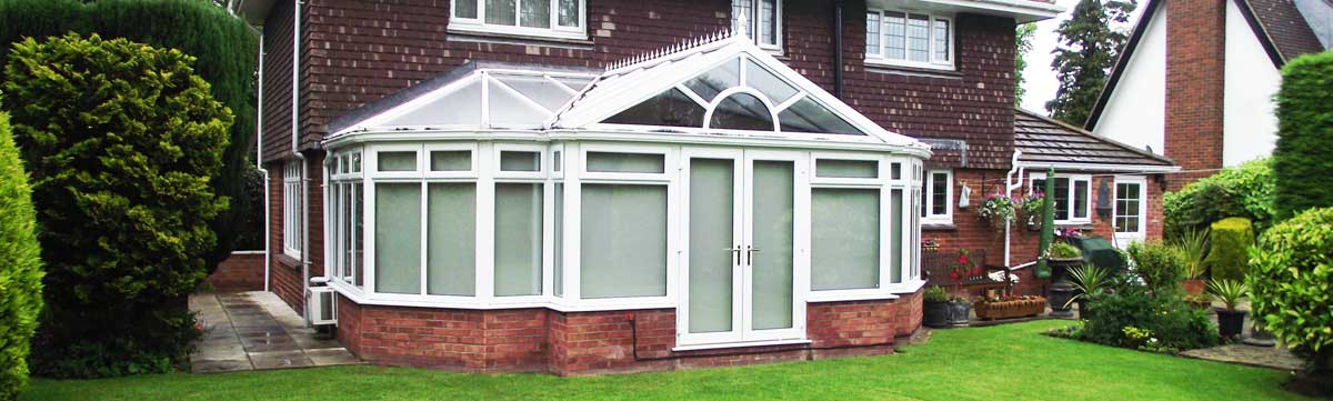 Large conservatory at rear of house with a garden scene